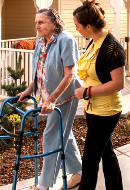 Resident and Staff - walking together in our secured outdoor courtyard.