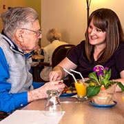 Resident having lunch with caregiver at Parkview Memory Care